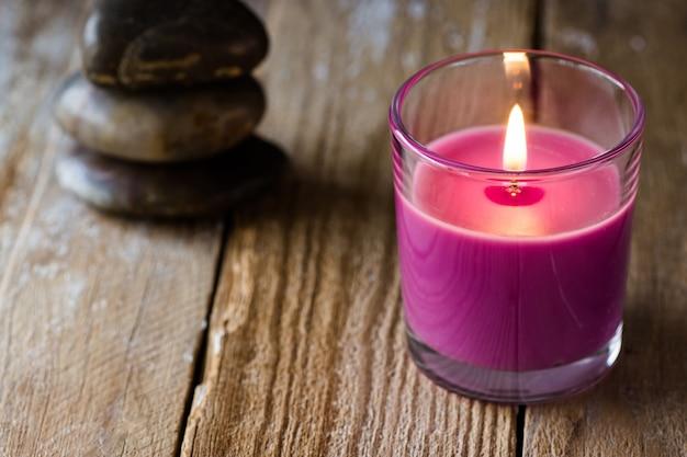 De brandende lilac stapel van de lavendelkaars evenwichtige zenstenen op houten achtergrond Premium Foto
