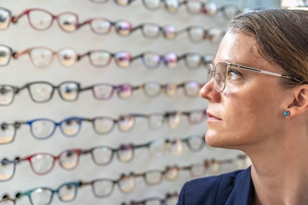 De bril wordt geselecteerd en getest door een vrouw in een optiekwinkel Premium Foto
