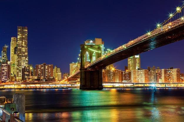 De brug van brooklyn bij schemer die van het park in de stad van new york wordt bekeken. Premium Foto