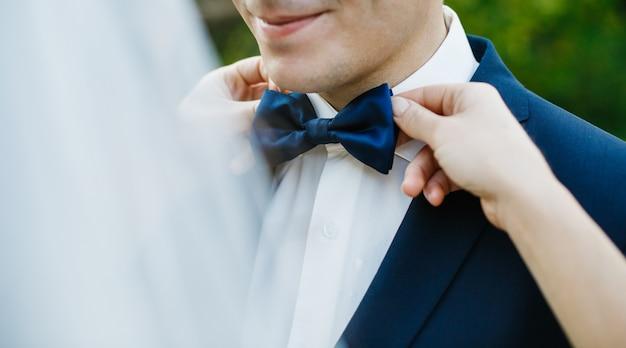 De bruid bevestigt blauwe vlinderdas op de hals van de bruidegom terwijl zij zich buiten bevinden Premium Foto