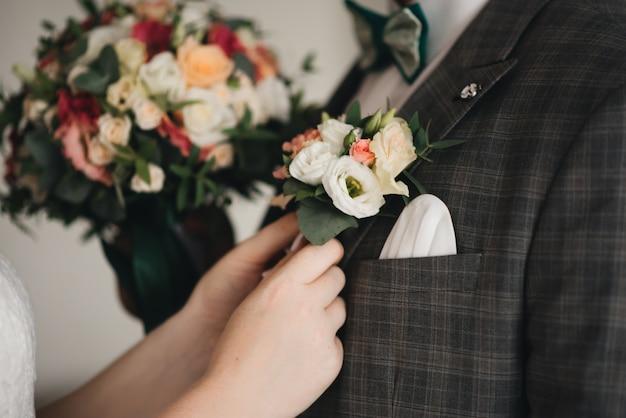 De bruid draagt een corsages voor de bruidegom. stijlvolle bruiloft ochtendfoto Premium Foto