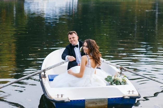 De bruid en bruidegom in een roeiboot op het meer Premium Foto