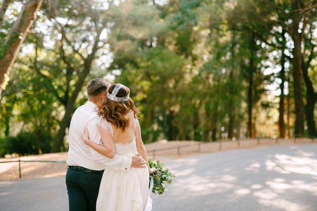 De bruid en bruidegom lopen langs de weg in het park en knuffelen elkaar, de bruid houdt vast Premium Foto