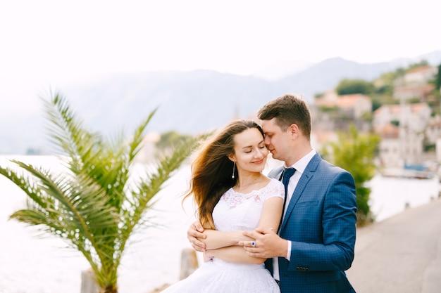 De bruid en bruidegom omhelzen elkaar op de pier in perast Premium Foto