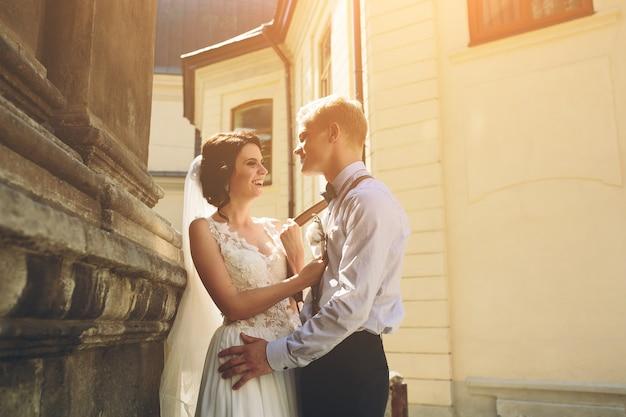 De bruid en bruidegom poseren in de oude straat Gratis Foto