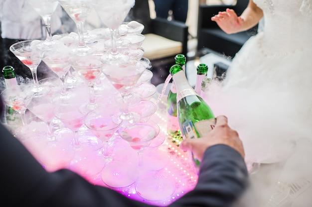 De bruid en bruidegom schenken champagne in glazen in een glaasje champagne Premium Foto