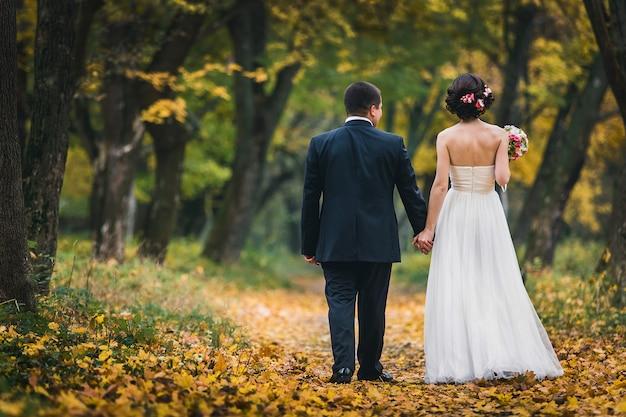De bruid en bruidegom staan met hun rug elkaar de hand vasthouden en wandelen in het park Premium Foto