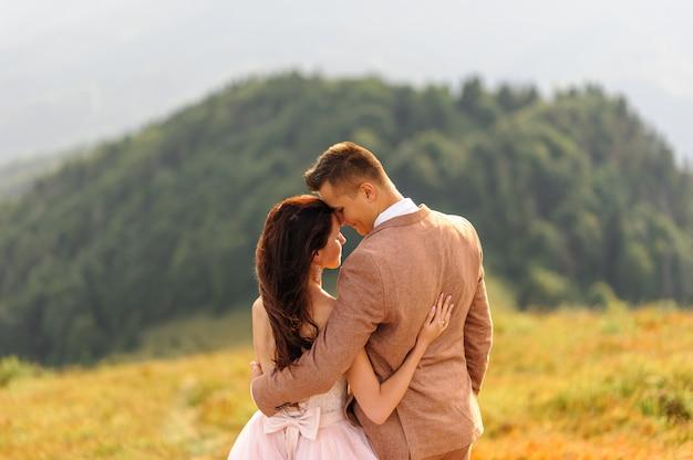 De bruid en bruidegom staan met hun rug en knuffelen. zonsondergang. huwelijksfoto op een achtergrond van de herfstbergen. een sterke wind blaast haar en jurk op. Premium Foto