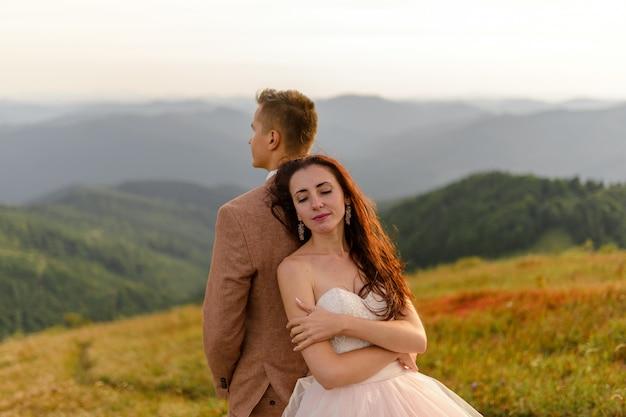 De bruid en bruidegom staan met hun rug naar elkaar toe. zonsondergang. huwelijksfoto op een achtergrond van de herfstbergen. een sterke wind blaast haar en jurk op. detailopname. Premium Foto