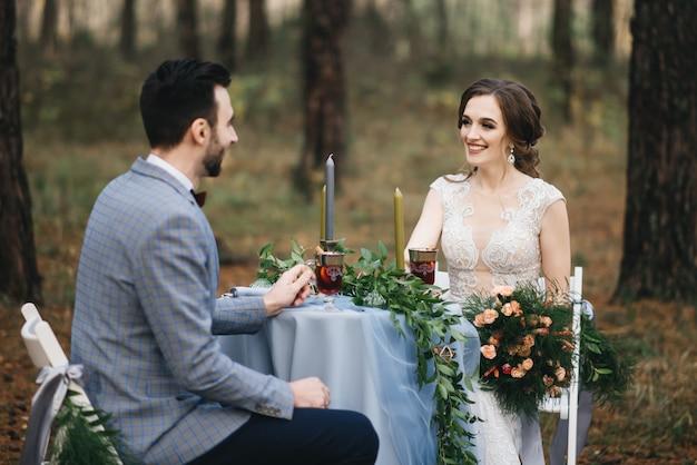 De bruid en bruidegom zitten aan een tafel voor twee in het bos. ze glimlachen en drinken glühwein. herfst. het concept van een romantische date Premium Foto