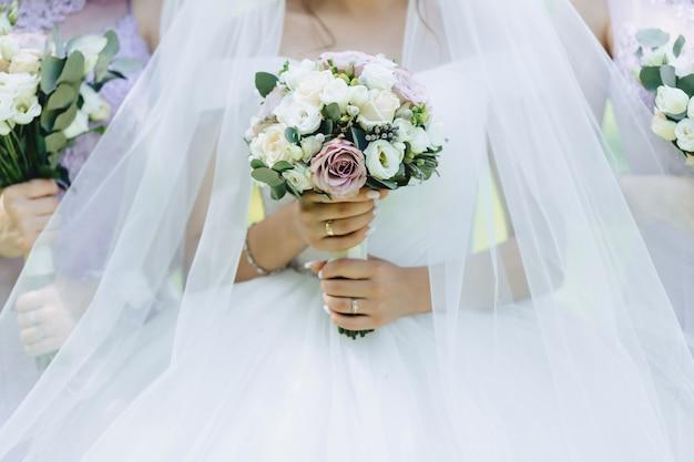 De bruid houdt een bruidsboeket in haar handen Gratis Foto