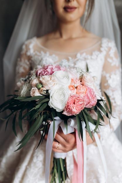 De bruid houdt het mooie bruidsboeket met witte en roze rozen Gratis Foto