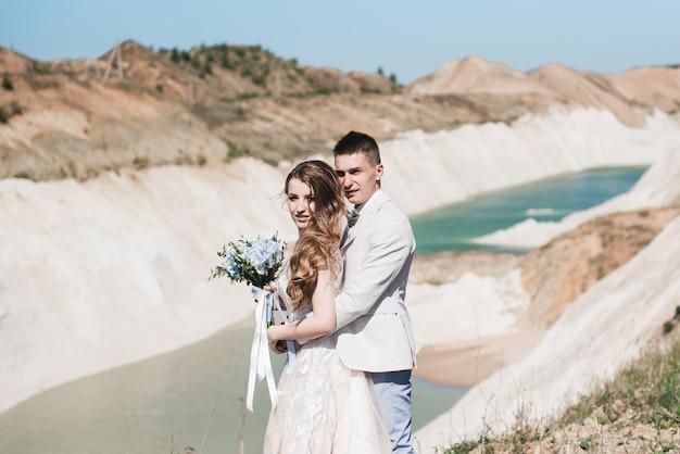 De bruid in een mooie jurk knuffelen de bruidegom in een licht pak in de buurt van het meer. bruidspaar staande op een zanderige heuvel in de open lucht. een romantisch liefdesverhaal. azuurblauw water aan de horizon. Premium Foto