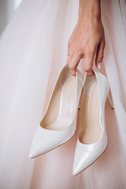 De bruid in haar trouwjurk houdt haar stijlvolle beige schoenen in haar handen. Premium Foto