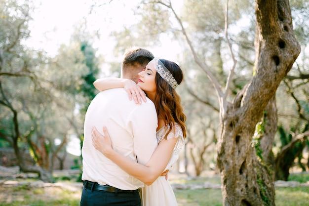 De bruid knuffelt zachtjes de bruidegom in het park en glimlacht. Premium Foto