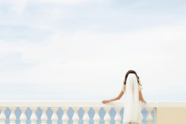 De bruid leunt over een wit balkon terwijl hij de zee bewondert Gratis Foto