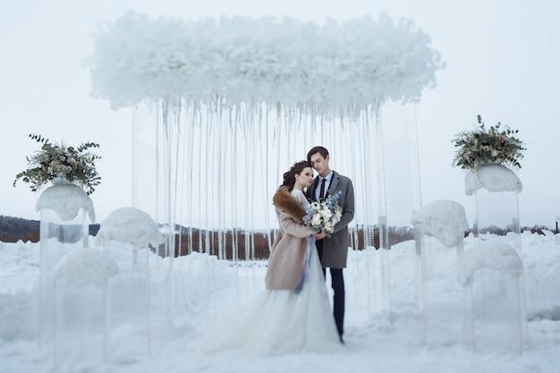 De bruid met een mooi boeket en de bruidegom op de bruiloft winter schieten. jongeren staan tegen de achtergrond van winter bruiloft decoraties Premium Foto