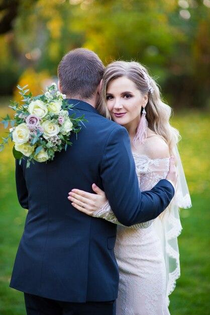 De bruid omhelsde haar bruidegom en kijkt vooruit Premium Foto