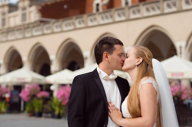 De bruid staat voor het gebouw Gratis Foto