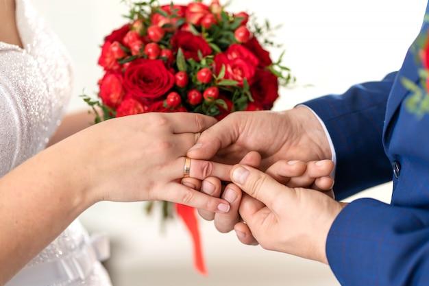 De bruidegom doet een trouwring aan de vinger van de bruid. bruiloft details. Premium Foto
