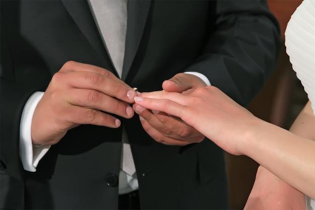 De bruidegom doet een verlovingsring om de vinger van de bruid Premium Foto