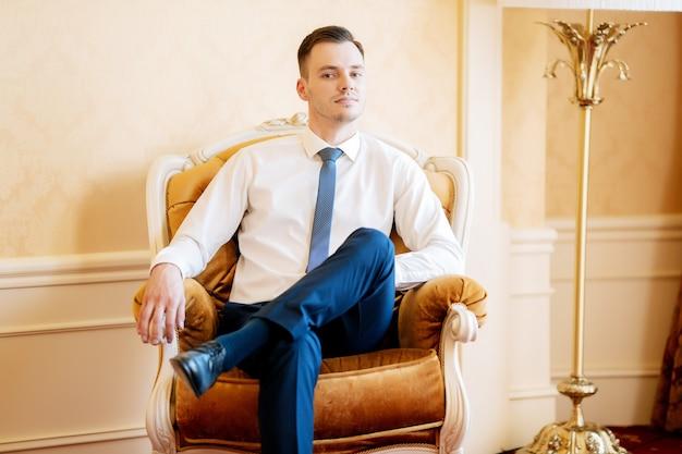 De bruidegom in een shirt zit op een stoel in het hotel Premium Foto