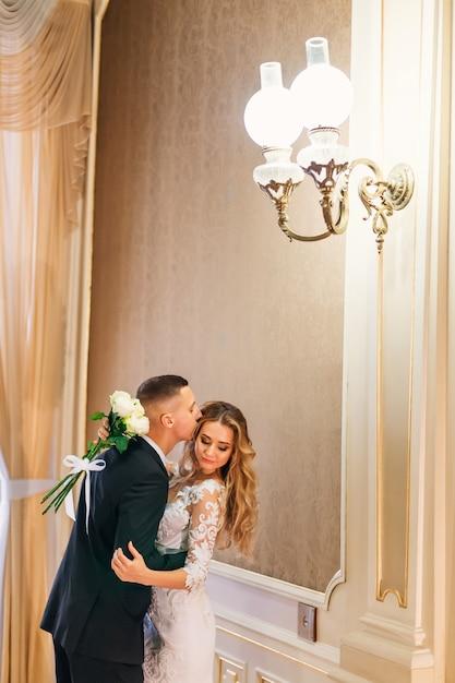 De bruidegom knuffelt en kust de bruid en ze sluit haar ogen en houdt een bruidsboeket vast Premium Foto
