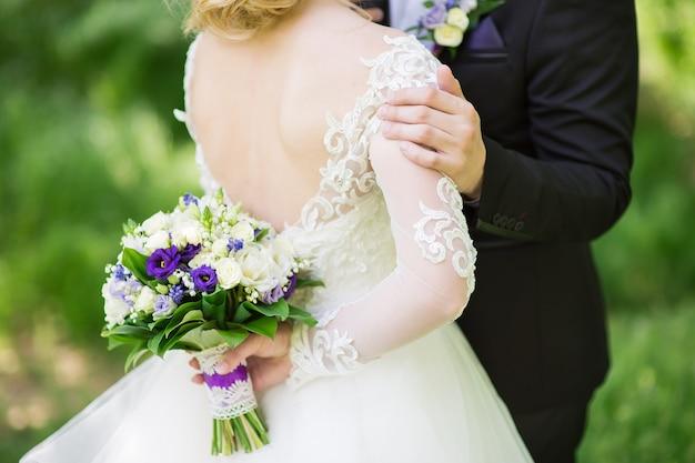 De bruidegom knuffelt zachtjes zijn bruid in de tuin Premium Foto