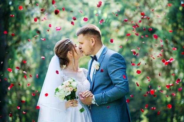 De bruidegom kust de bruid in rozenblaadjes Premium Foto