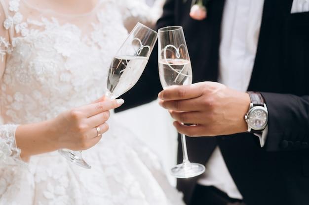 De bruidegom met bruid klopt glazen met champagne Gratis Foto