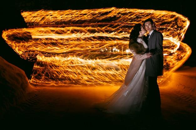 De bruidegom omhelst de bruid tegen de achtergrond van vlammen, staande in de sneeuw. techniek nachtfotografie door licht en lichtschildering te bevriezen. Premium Foto