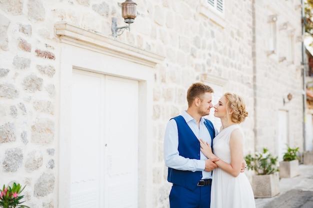 De bruidegom omhelst de bruid zachtjes tegen de achtergrond van een prachtig wit huis in perast. Premium Foto
