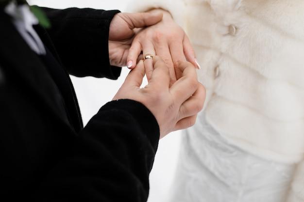 De bruidegom zet in openlucht de trouwring op van zijn toekomstige vrouw Gratis Foto
