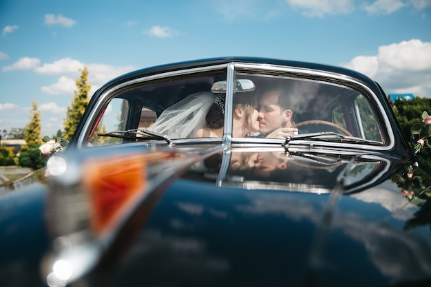 De bruiden kussen de auto op de trouwdag Gratis Foto