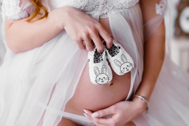 De buik van de zwangere vrouw met babysokken, moederhand die pasgeboren babysok, pasgeboren meisje houden Premium Foto