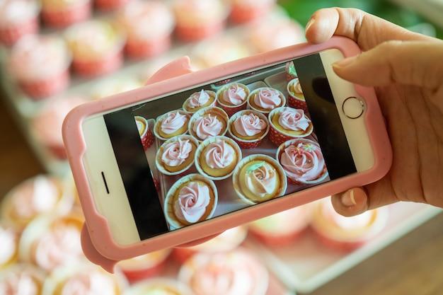 De café-eigenaar gebruikt een smartphone om foto's te maken van nieuw afgewerkte cupcakes om te promoten op online media en websites. producten online verkopen Premium Foto