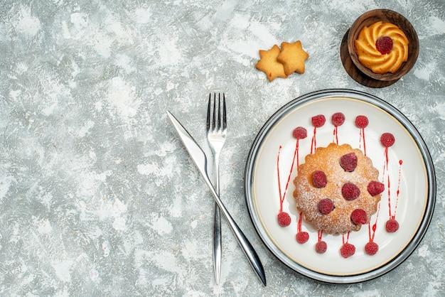 De cake van de hoogste meningsbes op wit ovaal plaatkoekje in kom gekruiste vork en dinermes op grijze oppervlakte vrije ruimte Gratis Foto