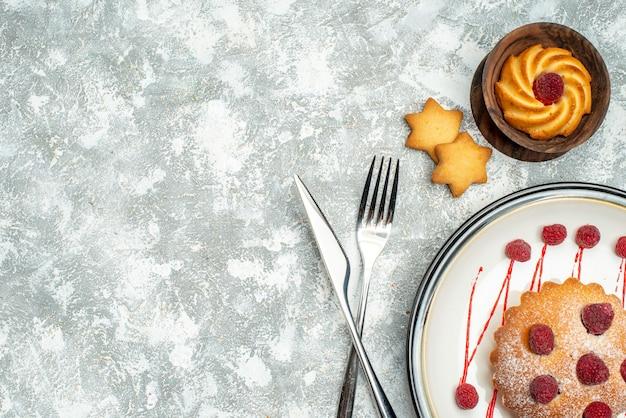 De cake van de hoogste meningsbes op witte ovale plaat gekruiste vork en dinermes op grijze oppervlakte vrije ruimte Gratis Foto