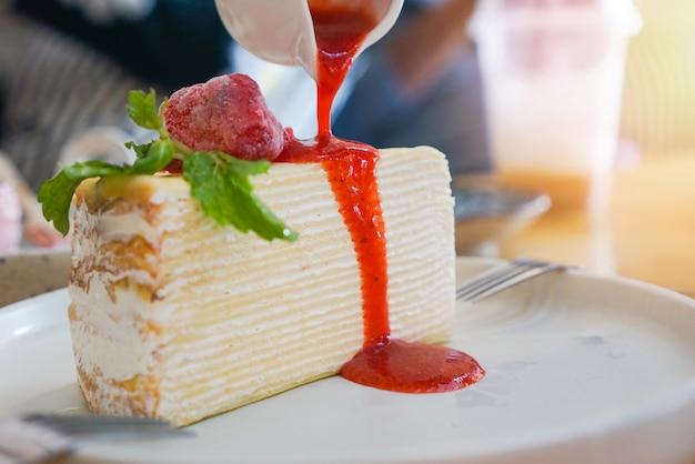 De cake van de rouwband met aardbeisaus op witte plaat op de lijstachtergrond - fluitje van een cent met slagroom Premium Foto