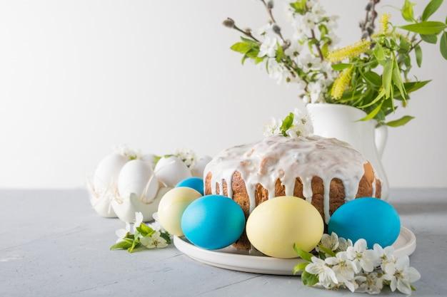 De cake van pasen, gekleurde eieren op de lijst van de gebeurtenisfamilie met kers komt bloemen tot bloei. ruimte voor tekst. Premium Foto