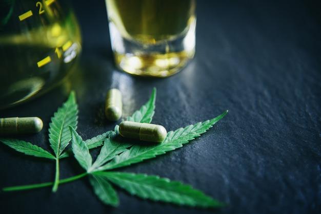 De cannabisplanthee en capsule van de marihuanablad cannabis op donkere achtergrond Premium Foto