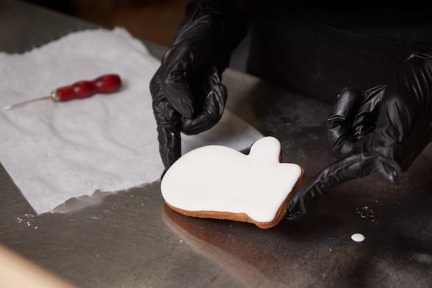 De chef-kok dient handschoenen in de keuken in die koekjes voorbereidt Premium Foto