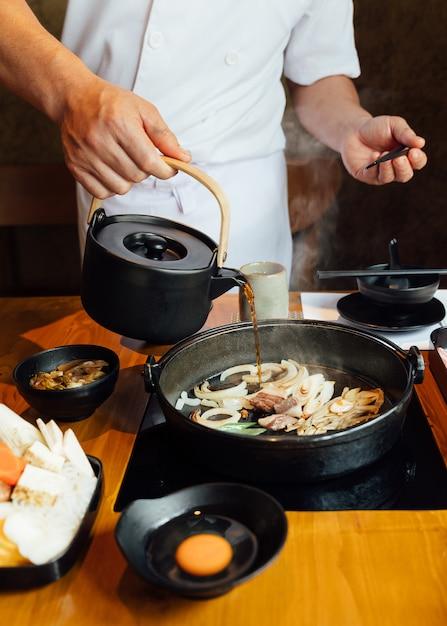 De chef-kok giet shabu-sausmengeling met gebraden ui, sjalot en rundvleesvet. Premium Foto