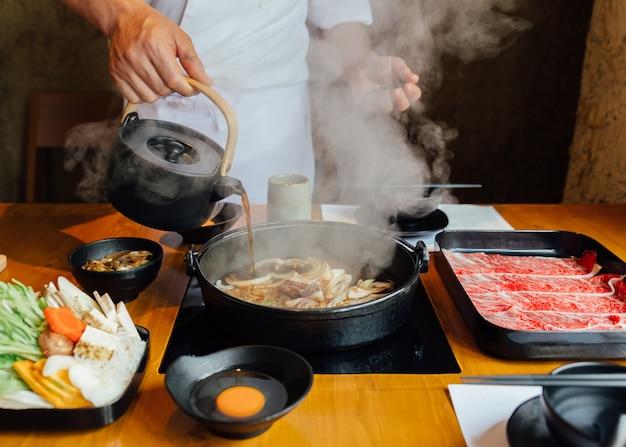 De chef-kok giet sojasaus op geroerde gebraden groenten zoals ui Premium Foto