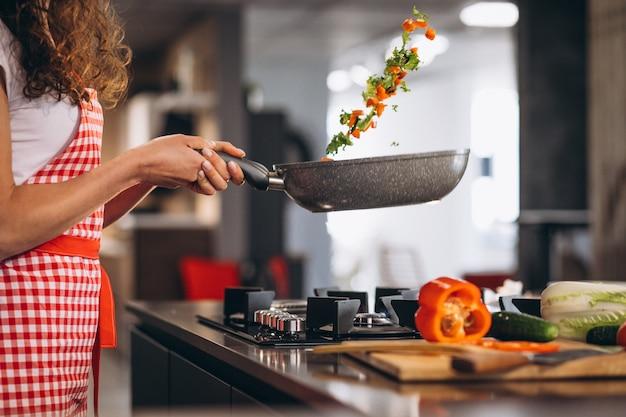 De chef-kok kokende groenten van de vrouw in pan Gratis Foto