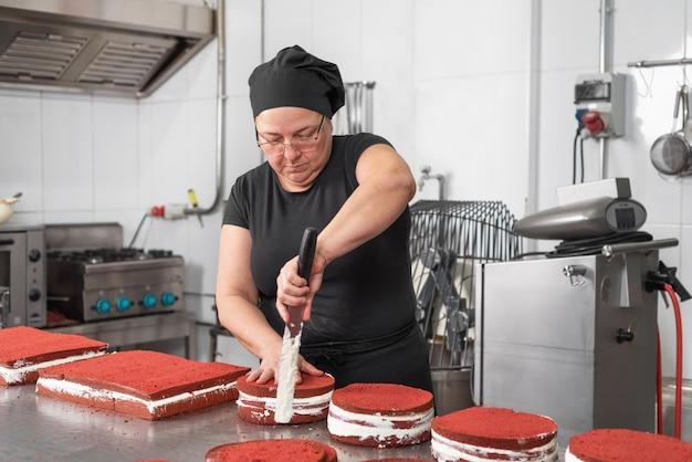 De chef-kok van het vrouwengebakje die en gelukkig glimlachen werken, makend cakes bij de patisserie. Premium Foto