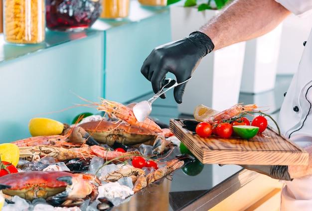 De chef-kok zet de zeevruchten op een dienblad in het restaurant. Premium Foto