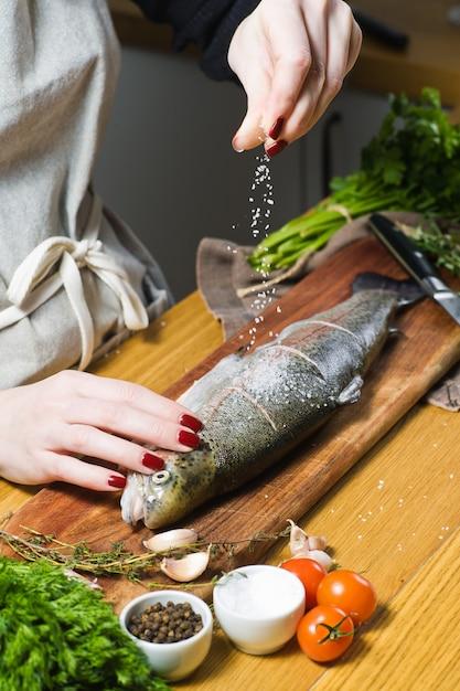 De chef-kok zouten rauwe forel op een houten snijplank. Premium Foto