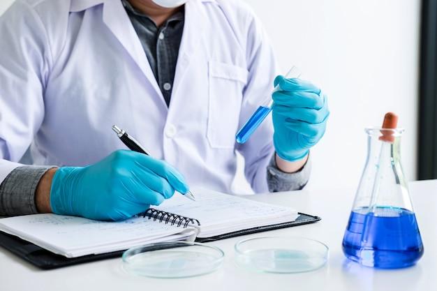 De chemicus analyseert steekproef in laboratorium met apparatuur en wetenschapsexperimenten Premium Foto