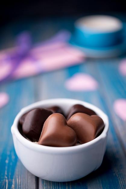 De chocolade van de valentijnskaartendag in kop met defocused heden Gratis Foto